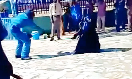 Screengrab from a YouTube clip of a woman being lashed in a carpark by police in Sudan.