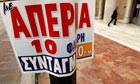 A man enters the Bank of Greece behind a banner calling for a 24-hour strike in Athens.