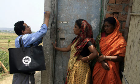 A census official marks a house at Hatkhuwapara Village, India
