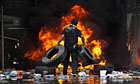 An anti-government protestor piles tires on a fire in Bangkok, Thailand