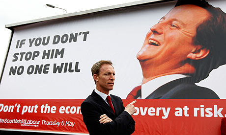 Secretary of state for Scotland Jim Murphy gestures towards a poster of David Cameron, in Edinburgh.