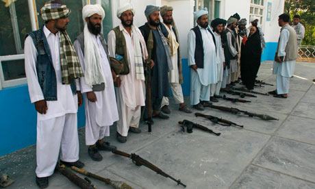 Afghanistani Taliban fighters surrender their weapons to authorities in Herat