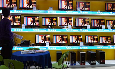 A salesman looks at LCD monitors at an electronics store in Hebei province.