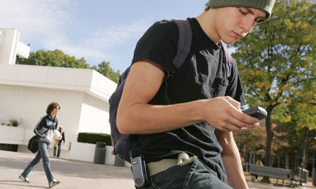 An American student checks in on his smart phone, above.