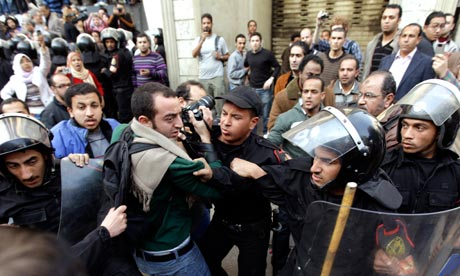 Riot police blocking press photographers during attempts to stage a second day of protests in Cairo