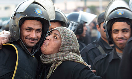 An Egyptian anti-government activist kisses a riot police officer following clashes in Cairo.