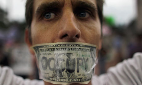 A demonstrator tapes a one dollar bill over his mouth in the Occupy Miami protest