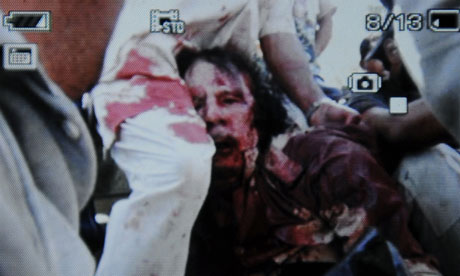 An image captured off a cellular phone camera shows the arrest of Gaddafi in Sirte