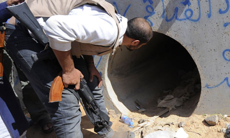 An NTC fighter looks through a large concrete pipe where ousted Gaddafi was allegedly captured