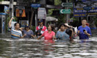 Bangkok residents wade through the city's flooded streets as water levels continue to rise.