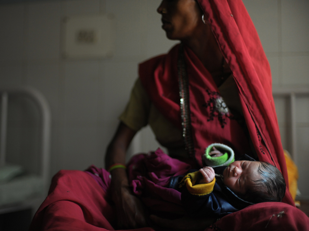 A new born baby sleeps in the arms of her mother at a Community Health Centre in Mall