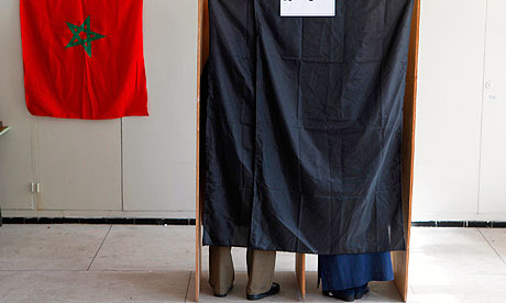 Moroccans stand inside voting booths before casting their votes at a voting station in Rabat