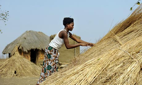 Joyce Musala, 18, prepares hay for a thatched roof in her village in Chibombo district, Zambia