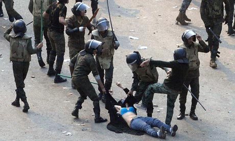 Egyptian army soldiers beating a female protester