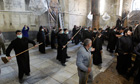 Armenian and Greek Orthodox clergy wielding brooms