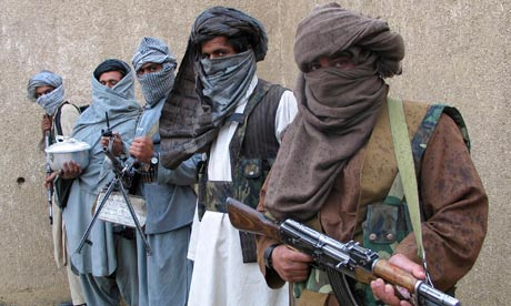 Taliban fighters hold their weapons