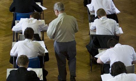 An invigilator passes out exam booklets to schoolchildren sitting an exam