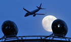 A British Airways passenger jet passes over the London Eye