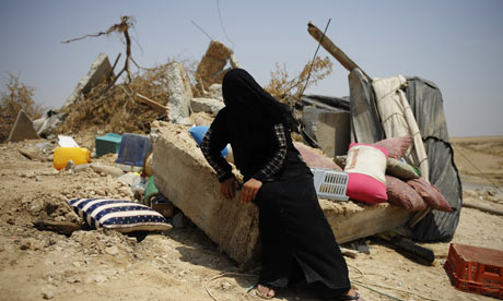 A Bedouin woman with the ruins of her home