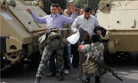Soldiers search anti-government protestors heading to Tahrir Square in Cairo