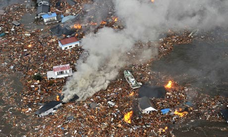 Flames rise from houses and debris from the tsunami in Sendai, Miyagi Prefecture