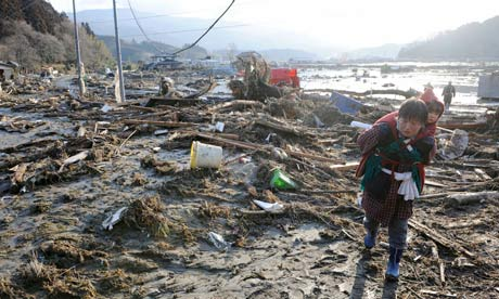A woman carrying a child on her back walks over debris in Rikuzentakada
