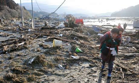 A woman carrying a child on her back walks over debris in Rikuzentakada