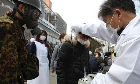 Official scans a woman for radiation in Fukushima