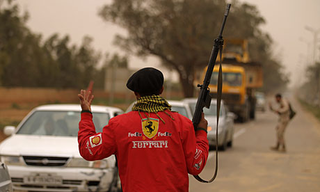 Libyan rebels direct people fleeing Benghazi as government troops move towards the eastern city.
