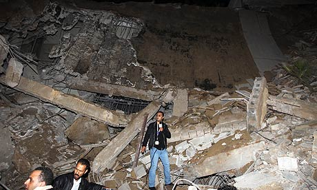 A journalist stands in the rubble of a building in Gaddafi's residence compound in Tripoli