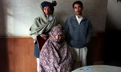 Lala Bibi with her father and son Saeed Ahmed – and photographs of her murdered son Najibullah and his cousin, who was also abducted. Photograph: Declan Walsh for the Guardian