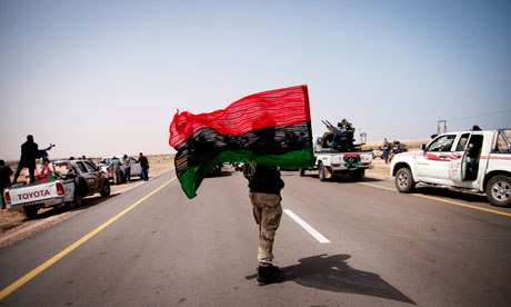 A Libyan rebel fighter holds the pre-Gaddafi flag in Al-Uqayla