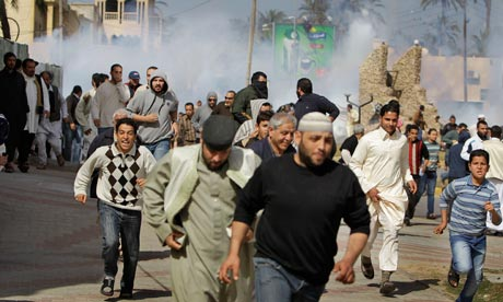 Anti-Gadhafi protesters run from tear gas fired by police