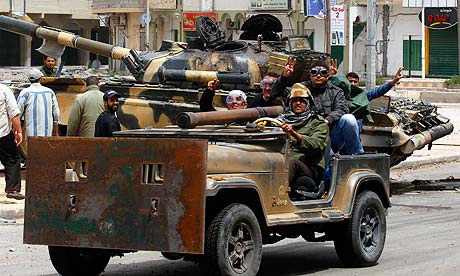 Rebel fighters drive past a captured government tank in Misrata.
