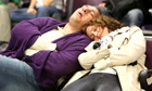 Airline passengers sleep as they wait for flights at Edinburgh airport in Scotland