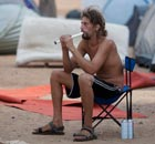 An Israeli man plays on a flute amid tents in Tel Aviv