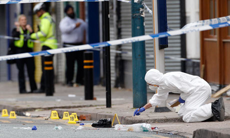 Riots in Birmingham : A police forensics officer inspects the scene where three men were killed