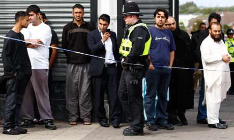 Riots in Birmingham : Men look at a police officer in the Winson Green area