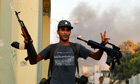 A Libyan rebel fighter flashes the victory sign at the Bab Al aziziya compound in Tripoli