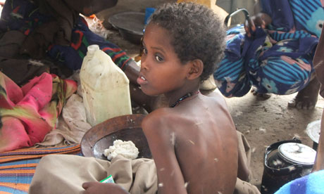 MDG : Somalia / A child from southern Somalia takes food at a camp in Mogadishu