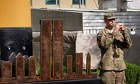 A soldier plays the trumpet next to a sculpture of the twin towers, a the US embassy in Kabul.