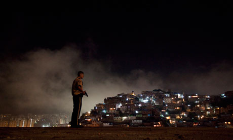 A policeman patrols a slum district of Caracas