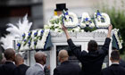 A man removes a floral tribute to Mark Duggan