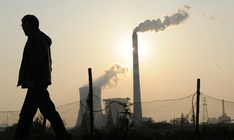 A man walks past as smoke billows from chimneys at a power station in Hefei, China