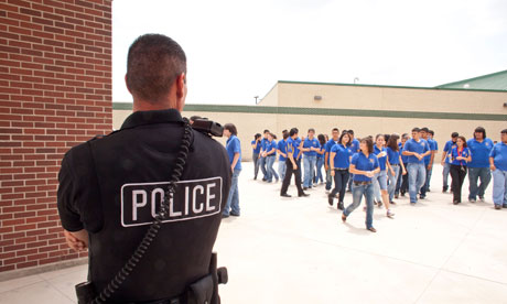 Male police officers supervise and keep an eye on students in South Texas high school
