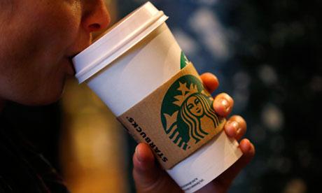 A customer sips her coffee in Starbucks' Mayfair Vigo Street branch in central London