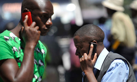 People use mobile phones in Nairobi, Kenya. There are about 700m sim cards in Africa.