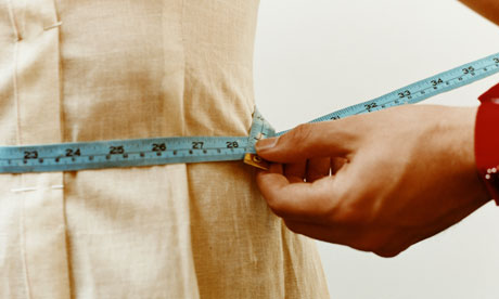 Measuring woman's waist with tape measure