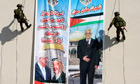 Palestinian security officers abseil past a banner of President Mahmoud Abbas with Yasser Arafat