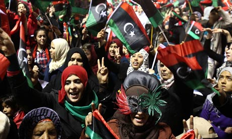 Libyans wave their new national flag in Tripoli marking one year since the revolution.